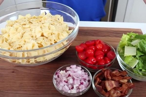 A tésztasaláta hozzávalói: tészta, hagyma, paradicsom, saláta és fűszerek